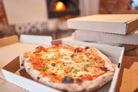 Pizza delivery concept. Baked products in a cardboard box against a wooden background. Baked tasty margherita pizza in Traditional wood oven in Neapolitan restaurant, Italy.