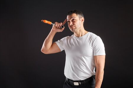 Athletic man with wrench on a black background. Not a typical worker, in a white t-shirt and trousers. Thumbs up Standard-Bild
