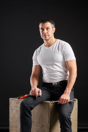 Athletic man with wrench on a black background. Not a typical worker, in a white t-shirt and trousers.