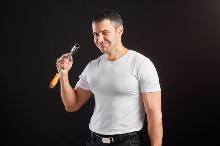 Athletic man with wrench on a black background. Not a typical worker, in a white t-shirt and trousers. Thumbs up Stockfoto