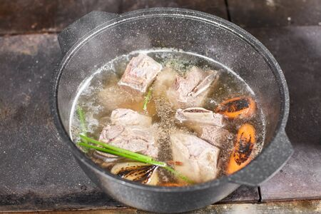 chef cook adds the ingredients. traditional beef broth with vegetable, bones and ingredients in pot, cooking recipe. Soup in a cooking pot with ladle on dark stone background. Top view Фото со стока