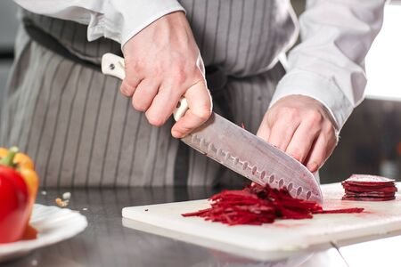 Closeup of hand with knife cutting fresh vegetable. Young chef cutting beet on a white cutting board closeup. Cooking in a restaurant kitchen Imagens