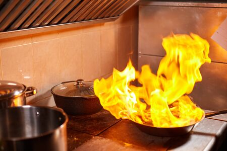 Flambe. Fire in frying pan. Professional chef in a commercial kitchen cooking. Man frying food in flaming pan on hob in outdoor kitchen Stockfoto