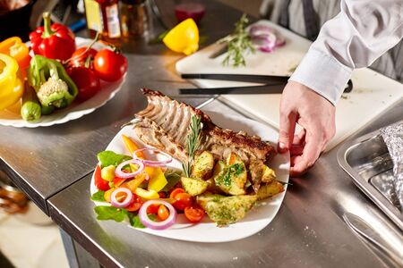 the chef prepares in the restaurant. Grilled rack of lamb with fried potatoes and fresh vegetables Stockfoto