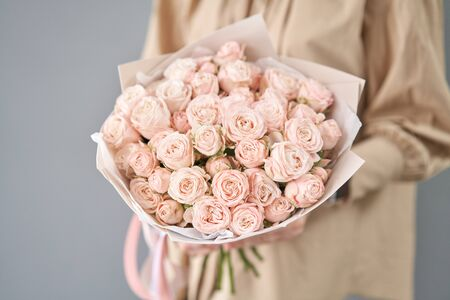 Mono bouquet of spray roses. Delicate bouquet of mixed flowers in womans hands. the work of the florist at a flower shop. Delicate Pastel color. Fresh cut flower. Stockfoto