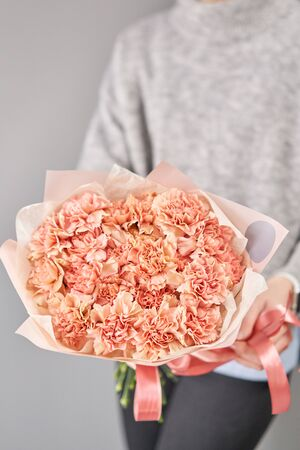 Bouquet of carnation flowers pastel color. Spring bunch in woman hand. Present for Mothers Day.