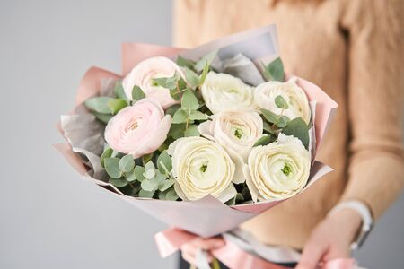 Persian buttercup in womans hands. Bunch pale pink ranunculus flowers with green eucalyptus. The work of the florist at a flower shop Stockfoto