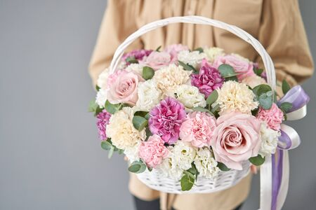 Flowers delivery. Flower arrangement in Wicker basket. Beautiful bouquet of mixed flowers in woman hand. Floral shop concept . Handsome fresh bouquet.