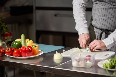 Young chef cutting beet on a white cutting board closeup. Cooking in a restaurant kitchen Stockfoto