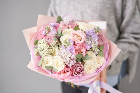 European floral shop. Beautiful bouquet of mixed flowers in womans hands. the work of the florist at a flower shop. Delivery fresh cut flower.