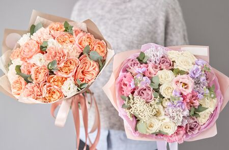 Two Beautiful bouquets of mixed flowers in womans hands. the work of the florist at a flower shop. Delivery fresh cut flower. European floral shop. Stockfoto
