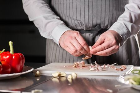 Closeup of hand with knife cutting fresh vegetable. Young chef cutting garlic on a white cutting board closeup. Cooking in a restaurant kitchen