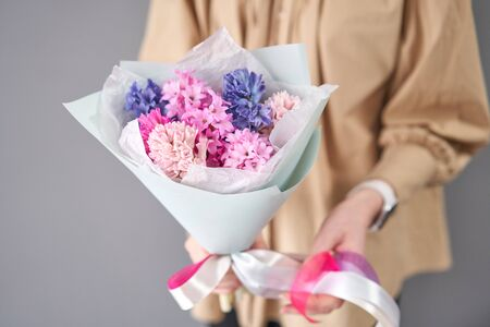 Young happy woman holding a beautiful bunch of colorful hyacinths in her hands. Present for a smiles girl. Flowers bouquet.