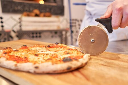 Italian kitchen and cooking concept. Chief with a pizza cutter cutting pizza to pieces at Neapolitan pizzeria Reklamní fotografie
