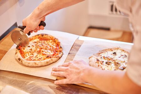 Italian kitchen and cooking concept. Chief with a pizza cutter cutting pizza to pieces at Neapolitan pizzeria 免版税图像