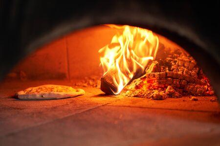 Pieczona smaczna pizza margherita w tradycyjnym piecu opalanym drewnem w restauracji Neapol, Włochy. Oryginalna pizza neapolitańska. Czerwony gorący węgiel