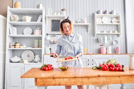Piękna młoda kobieta przygotowuje sałatkę jarzynową w kuchni. Zdrowe jedzenie. Gotowanie w domu. Koncepcja diety. Zdjęcie Seryjne