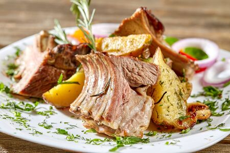 Grilled rack of lamb with fried potatoes and fresh vegetables. Dinner at restaurant.
