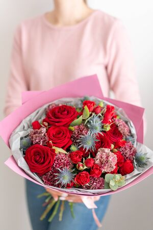 Mixed bouquet of red tones. Beautiful bunch of fresh flowers in womans hands. The work of the florist at a flower shop. Fresh cut flower Banco de Imagens