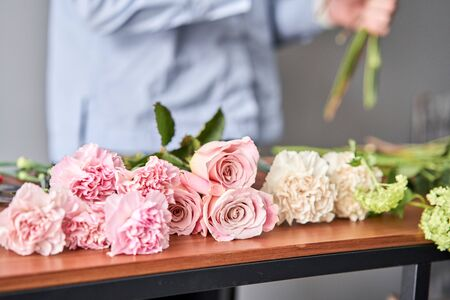 European floral shop. Beautiful bouquet of mixed flowers in womans hands. the work of the florist at a flower shop. Delivery fresh cut flower