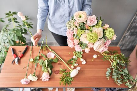Education in the school of floristry. Master class on making bouquets. Summer bouquet. Learning flower arranging, making beautiful bouquets with your own hands. Flowers delivery. Banque d'images - 140648149