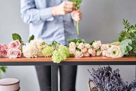 Education in the school of floristry. Master class on making bouquets. Summer bouquet. Learning flower arranging, making beautiful bouquets with your own hands. Flowers delivery. Banque d'images - 140648156