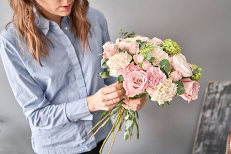Education in the school of floristry. Master class on making bouquets. Summer bouquet. Learning flower arranging, making beautiful bouquets with your own hands. Flowers delivery. Banque d'images - 140648488