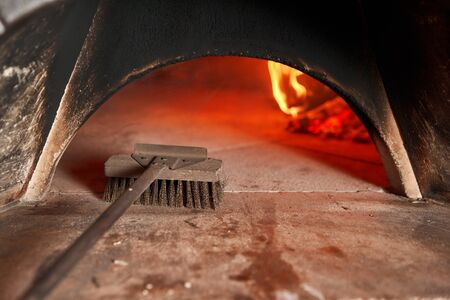 Pizza Chef cleaning pizza oven with special brush. Traditional wood oven in restaurant, Italy. Original neapolitan pizza. Red hot coal. Stok Fotoğraf