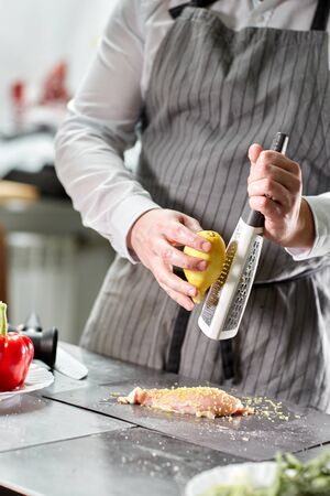 Chief chops and marinates chicken. Professional chef in a kitchen of restaurant cooking. Stok Fotoğraf