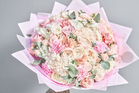 European floral shop. Beautiful bouquet of mixed flowers in hands. the work of the florist at a flower shop. Delivery fresh cut flower.