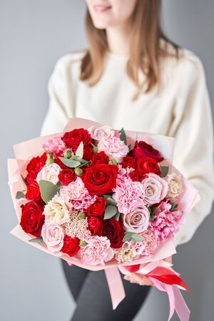 European floral shop. Red and pink Beautiful bouquet of mixed flowers in womans hands. the work of the florist at a flower shop. Delivery fresh cut flower.
