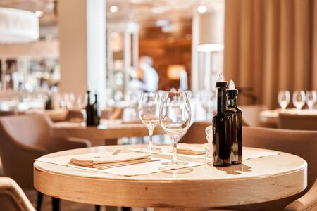 Wine glasses in the foreground. The chairs and table for guests, served with cutlery and crockery