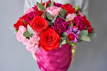 Red and violet floral bunch in Velour round box. European floral shop. Bouquet of beautiful Mixed flowers in woman hand. Banco de Imagens