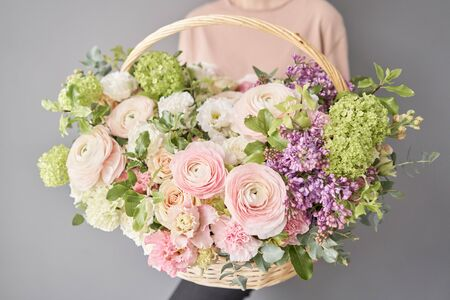 Flowers delivery. Flower arrangement in large Wicker basket. Beautiful bouquet of mixed flowers in woman hand. Floral shop concept . Handsome fresh bouquet.