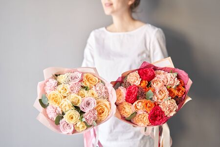 Two Beautiful bouquets of mixed flowers in womans hands. the work of the florist at a flower shop. Delivery fresh cut flower. European floral shop. Banco de Imagens
