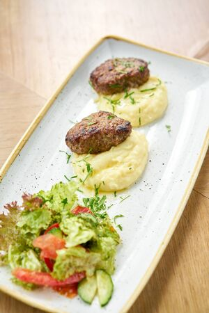 Delicious juicy meat cutlets, mashed potatoes sprinkled with greens and fresh healthy salad of tomatoes and lettuce leaves