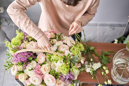 Floral shop concept . Florist woman creates flower arrangement in a wicker basket. Beautiful bouquet of mixed flowers. Handsome fresh bunch. Flowers delivery.