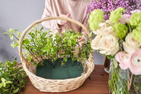 Floral shop concept . Florist woman creates flower arrangement in a wicker basket. Beautiful bouquet of mixed flowers. Handsome fresh bunch. Flowers delivery