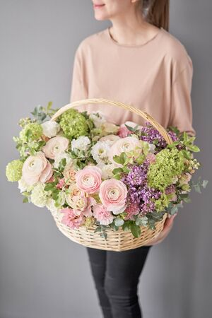 Flowers delivery. Flower arrangement in large Wicker basket. Beautiful bouquet of mixed flowers in woman hand. Floral shop concept . Handsome fresh bouquet Фото со стока