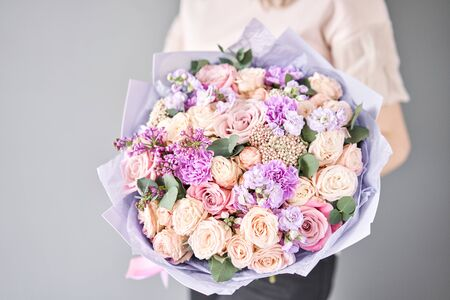 European floral shop. Beautiful bouquet of mixed flowers in womans hands. the work of the florist at a flower shop. Delivery fresh cut flower. Banco de Imagens