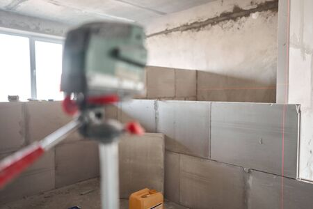 The construction worker Measures horizon level with a laser level. Construction of internal walls in the apartment using a plaster concrete plate with groove ridge.