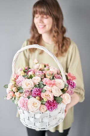 Small flower shop and Flowers delivery. Flower arrangement in Wicker basket. Beautiful bouquet of mixed flowers in woman hand. Handsome fresh bouquet. Stock Photo