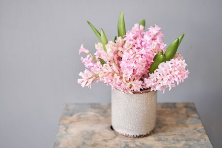 Bouquets of pink hyacinths in vase on wooden table. Spring flowers from Dutch gardener. Concept of a florist in a flower shop. Wallpaper. Archivio Fotografico