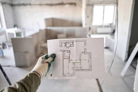The construction worker hold in hands Architectural blueprints. Repair or construction of a new apartment. Concept for new house design or home improvement. Development of the apartment project