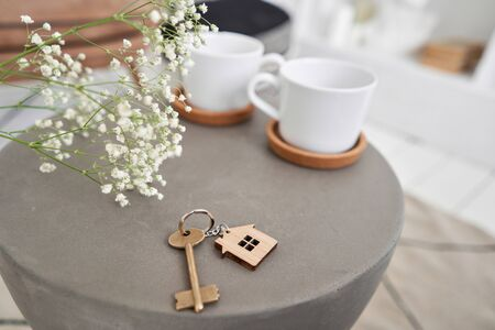 Stay home. House key and keychain in the form of homes lies on concrete table. Concept for real estate, mortgage, moving home or renting property. Bed and Breakfast Banque d'images