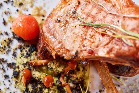 Pork meat on the bone with baked potatoes decorated with pickled cherry tomatoes. Photos for cafe and restaurant menus Archivio Fotografico