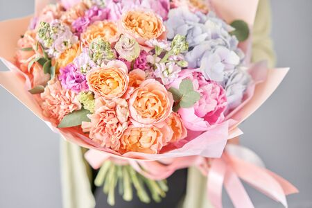 Pink peonies and hydrangea. Beautiful bouquet of mixed flowers in woman hand. Floral shop concept . Handsome fresh bouquet. Flowers delivery. Фото со стока