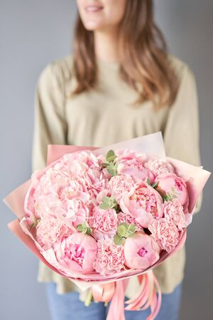 Bouquet of pink peonies and carnations in womans hands. Modern floral shop. Finished work of the florist. Delivery fresh cut flower from online store Standard-Bild - 149890258