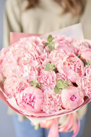 Bouquet of pink peonies and carnations in womans hands. Modern floral shop. Finished work of the florist. Delivery fresh cut flower from online store Standard-Bild - 149890166