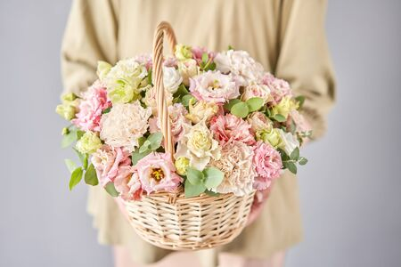 Small flower shop and Flowers delivery. Flower arrangement in Wicker basket. Beautiful bouquet of mixed flowers in woman hand. Handsome fresh bouquet. Standard-Bild - 149889236